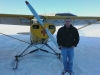 Pilot RJ Dreimiller is standing with his PA11, equipped with skis